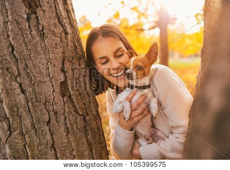 Portrait Of Young Happy Woman Holding Little Cute Dog
