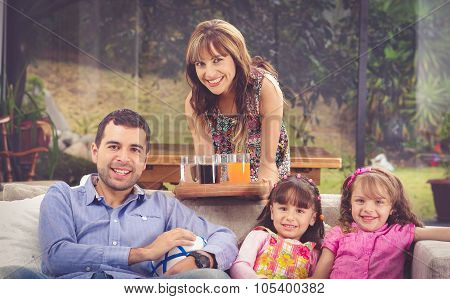 Hispanic father sitting in sofa with two daughters and mother leaning over from behind serving tray