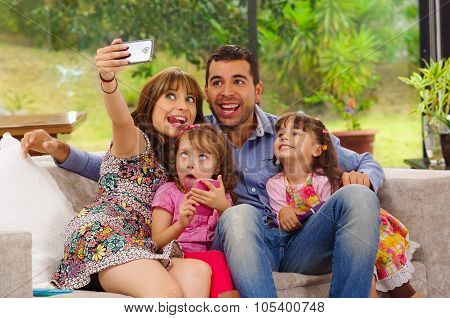 Family portrait of father, mother and two daughters sitting together in sofa