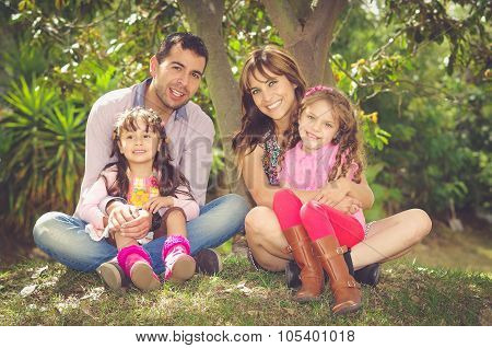 Beautiful hispanic family of four sitting outside on grass engaging in conversations while posing na