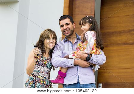 Adorable hispanic family of three posing for camera outside front entrance door