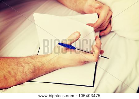 Handsome man writing a note in bed.