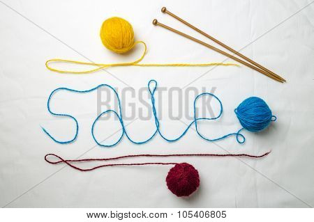 Word sale written multicolored yarn threads coiled into balls on a white background