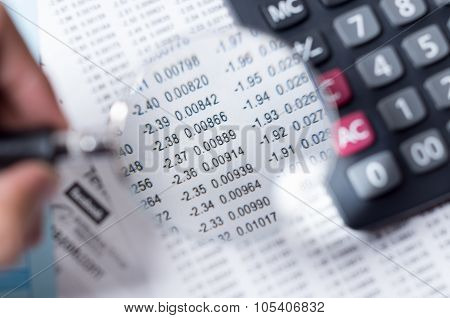 Closeup magnifying glass over paper with numbers and calculator sitting besides