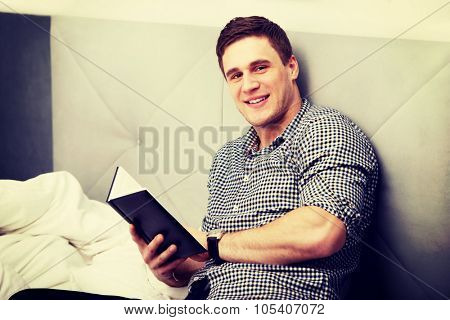 Handsome thoughtful man with a note in his bed.