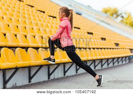 Portrait of a sports woman warming up at outdoor stadium