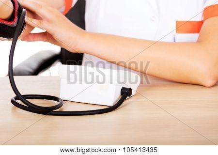 Female doctor or nurse sitting behind the desk holding blood pressure gauge.