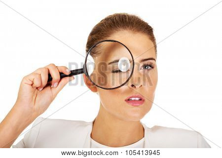 Businesswoman looking into a magnifier and have a big eye.