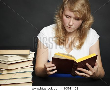 Young Woman Reads Book Against Dark Background