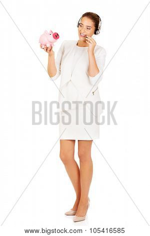Young businesswoman in headset holding piggybank.