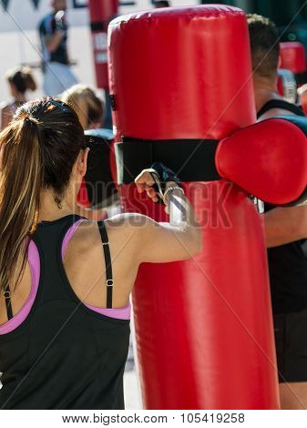 Young Woman And Punching Bag: Female Kickboxing Exercise