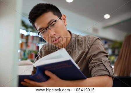 Portrait of a handsome asian male student reading book in university