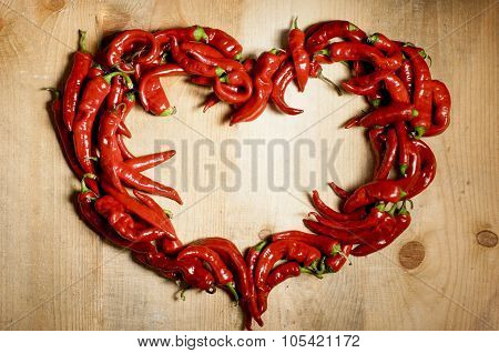 Heart Shape From Chili Is Laid  On Wooden Backgorund.