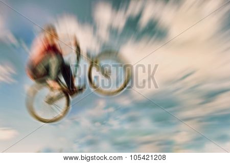Abstract Background. Boy On A Bmx Mountain Bike Jumping. Motion Blur Photo