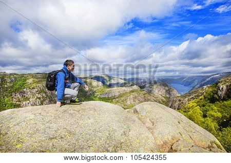 A young man on the mountain admiring view over Lysefjord. Norway.