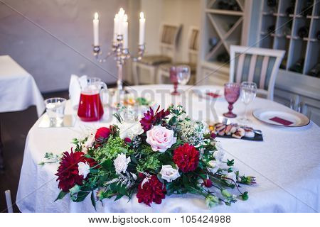 interior of the restaurant,  large table laid for  Banquet, decorated in Burgundy tones