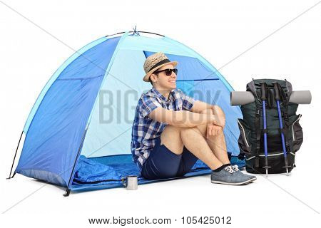 Cheerful male hiker sitting on the floor in front of a blue tent with his backpack and hiking equipment beside him isolated on white background