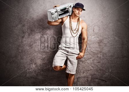 Young male rapper in hip-hop outfit listening to music from a ghetto blaster and leaning against a rusty gray concrete wall