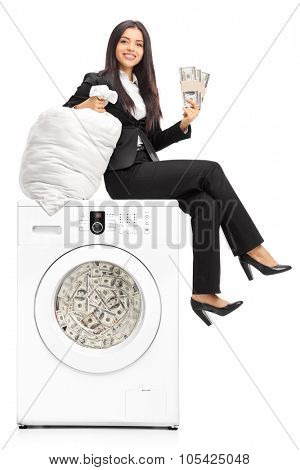 Young businesswoman laundering money in a washing machine and looking at the camera isolated on white background