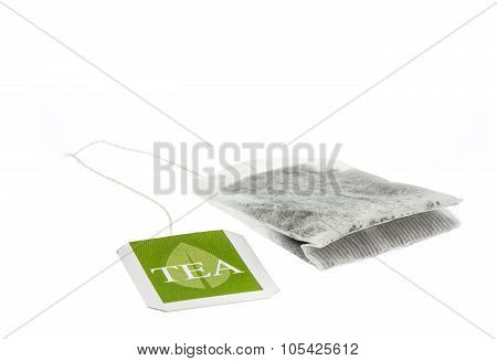 Tea paper sachet with green label isolated on white background