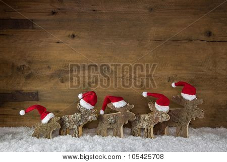 Rustic old wooden background. Christmas decoration in red white and a group of santa in the snow.