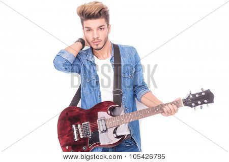 relaxed guitarist with hand behind his neck, looking at the camera on white background