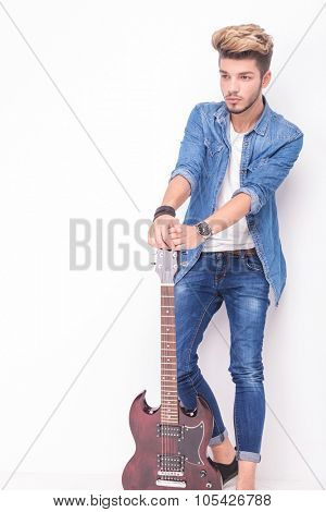 side view of a young guitarist taking a break and looks away from the camera on white background