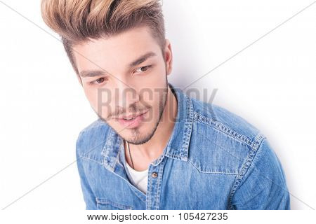 face of a young casual man smiling looking to side away from the camera
