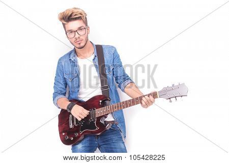 cool casual guitarist playing his red electric guitar on white studio background