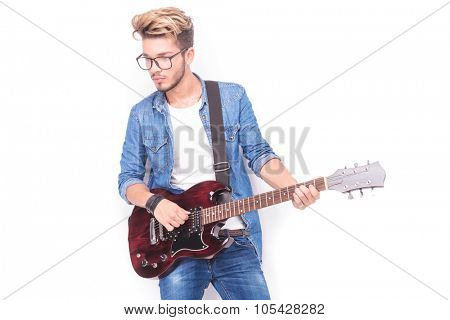 young casual guitarist playing his electric guitar and looks to his side on white background, wearing jeans clothes and glasses