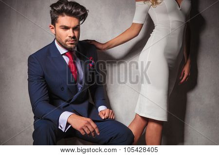 young elegant man sitting and his woman leaving him, walking away in studio