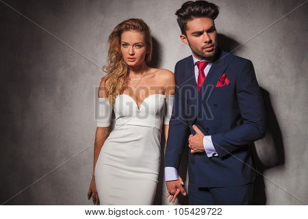 macho fashion elegant man holding his lover by her hand and looks to a side, sexy woman is looking at the camera in studio