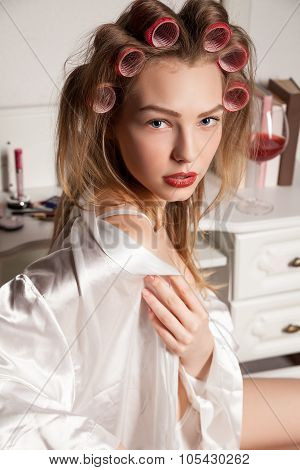 Fashion photo of beautiful blond woman with curler in the hair
