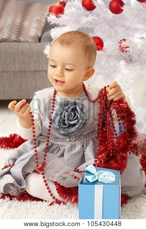 Pretty little girl playing with christmas ornaments under christmas tree.