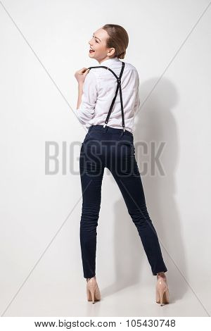fashion model in black trousers and top posing over white. Back view