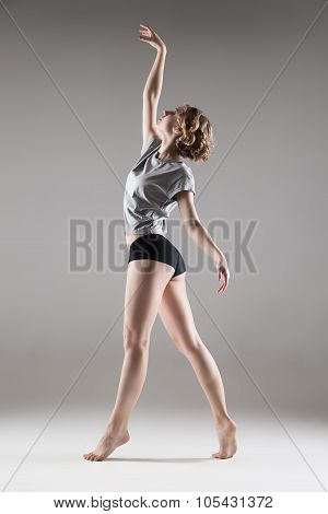 young beautiful woman in grey T-shirt and black shorts dancing