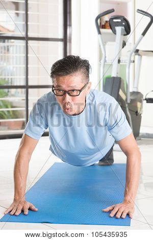 Portrait of active 50s mature Asian man in sportswear doing pushup on exercise mat, workout at indoor gym room.