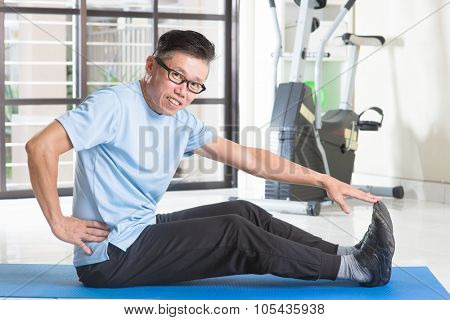 Portrait of sporty 50s mature Asian man in sportswear doing leg stretching on exercise mat, workout at indoor gym room.