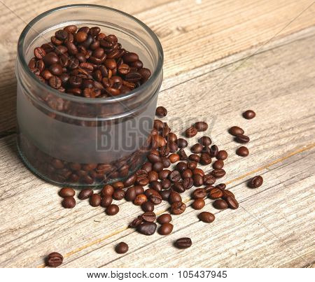 coffee beans in a glass jar on a wooden table