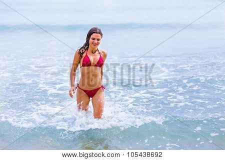 Young woman walking in the Mediterranean sea
