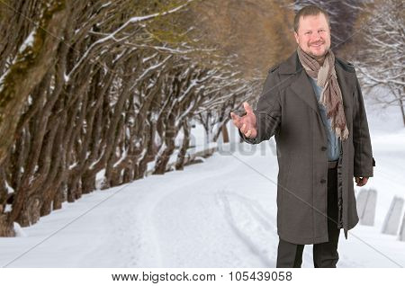 Middle-aged man in a coat looking friendly on winter park background