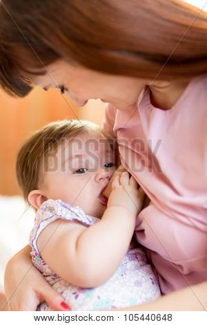 Happy mother feeding breast baby at home