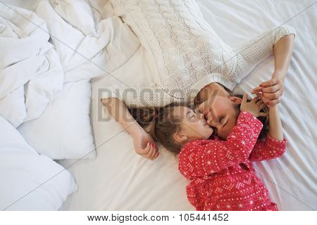 Mom with her 6 years old little daughter dressed in winter pajamas are relaxing and playing in the bed at the weekend together, lazy morning, warm and cozy scene. Top view point.