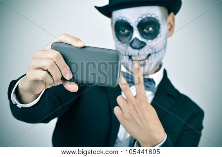 a young man with calaveras makeup, wearing bow tie and top hat, takes a selfie of himself with a smartphone