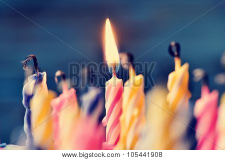 closeup of some unlit candles and just a lit candle after blowing out the cake