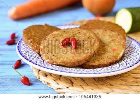 closeup of some raw veggie burgers in a plate on a blue wooden table, with some vegetables in the background