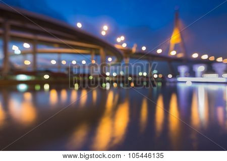 Abstract blurred bokeh light of suspension bridge with water reflection during twilight