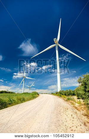 Green renewable energy concept - wind generator turbines in real landscape with grass and road, vertical