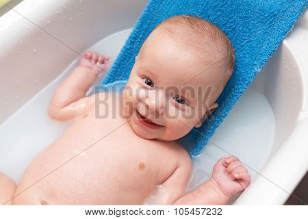 Happy baby boy having a bath