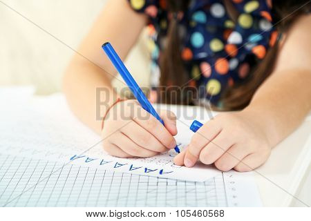 Cute little girl doing her homework, close-up
